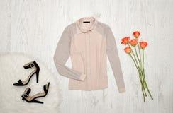 Rosa färg- och grå färgblus, skor och orange rosor på en träbakgrund trendigt begrepp Royaltyfri Fotografi