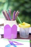 Rosa färg- och gulingask av blyertspennor och borstar Arkivbilder