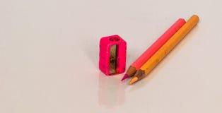 ROSA FÄRG- och gulingblyertspennan, vässare är Arkivfoto