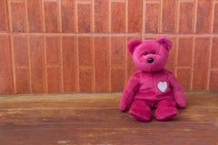 Rosa färgbjörnleksak bara på träbakgrunder Arkivfoton