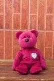 Rosa färgbjörnleksak bara på träbakgrunder Royaltyfri Foto