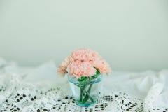 Rosa färgen blommar i blått exponeringsglas Arkivfoto