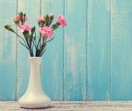 Rosa färgen blommar i en vas på blå bakgrund royaltyfria bilder