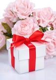 Rosa färgen blommar och gåvaasken med det röda bandet och pilbågen på vita lodisar Royaltyfri Foto