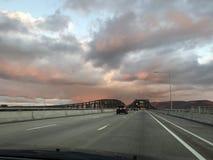 Rosa färgen fördunklar över en huvudvägbro Royaltyfria Bilder