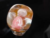 Rosa färger bäddade in ett stycke av is Arkivfoton