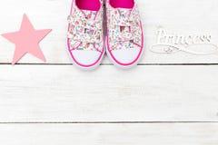 Rosa färger behandla som ett barn gymnastikskor och bokstäver på en vit träbakgrund C arkivfoton