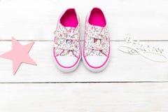 Rosa färger behandla som ett barn gymnastikskor och bokstäver på en vit träbakgrund f arkivfoton