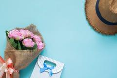 Rosa färger blommar buketten, och gåvan på blå bakgrund, den speciala dagen lurar arkivfoton