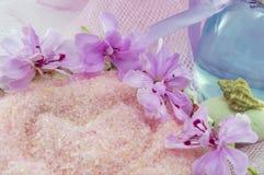 Rosa färger blommar runda rosa salt för bad med etheric olja i en flaska Arkivfoton