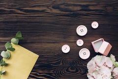 Rosa färger boxas för förlovningsring, knappar och vanlig hortensia på trätabellen, bästa sikt Utrymme för text Royaltyfri Fotografi