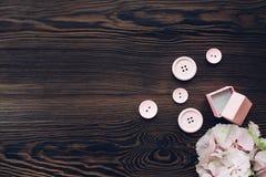 Rosa färger boxas för förlovningsring, knappar och vanlig hortensia på trätabellen, bästa sikt Utrymme för text Arkivfoto