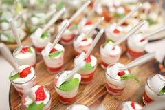 Rosa färger färgad jordgubbeefterrätt i skottexponeringsglas som sköter om buffé Royaltyfri Foto