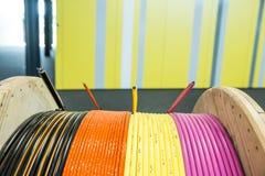 Rosa färger, guling, apelsin och bestrukna kablar för svart på den Wood rullen royaltyfria foton