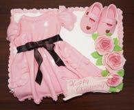 Rosa färger klär kakan med skor och blommor för att döpa och dop Arkivfoton