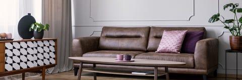 Rosa färger kudde på lädersoffa i vardagsruminre med växten på den near tabellen för skåpet Verkligt foto arkivbild