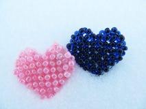 Rosa färger och blått prydde med pärlor hjärta i snön Arkivbilder