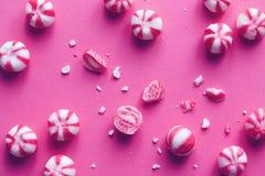 Rosa färger och vit gjorde randig sötsaker på rosa bakgrund Royaltyfria Bilder