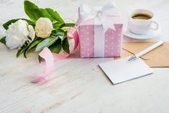 Rosa färger prack gåvaasken, det tomma hälsningkortet, det kraft kuvertet, pionbuketten och kaffekoppen över den vita trälantliga Royaltyfri Fotografi