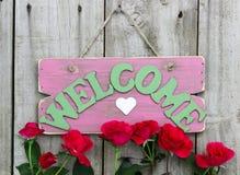 Rosa färger red ut det välkomna tecknet med hjärta som hänger på dörr med blommagränsen av röda rosor Arkivfoto