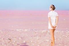 Rosa färger saltar sjö- och younfkvinnan i vit arkivfoton