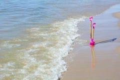 Rosa färger skyfflar i sanden Arkivbild