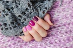 Rosa färger spikar design Härlig kvinnlig hand med olika skuggor av rosa manikyr Fotografering för Bildbyråer