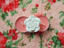 Rosa färger vädrade stearinljus med den vita blomman i mitt arkivbild