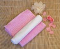 Rosa färger vit handduk med kronbladet på matt bambu royaltyfri bild