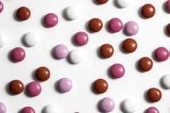 Rosa färger, vit och röda bestrukna choklader Royaltyfri Bild