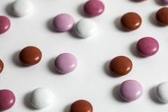 Rosa färger, vit och röda bestrukna choklader Arkivbild