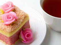 Rosa färgkaka och en kopp te Arkivbilder