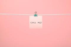Rosa färgpappersanmärkningen på raden med text kallar mig! Fotografering för Bildbyråer