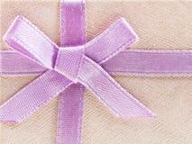Rosa färgpilbåge på den glänsande pappers- gåvaasken Arkivfoto
