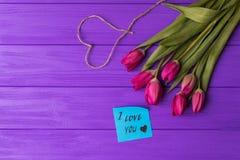 Rosa färgrika tulpan över en purpurfärgad bakgrund, i sänker lekmanna- sammansättning med hjärta och inskriften på papper som jag Royaltyfri Bild