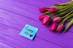 Rosa färgrika tulpan över en purpurfärgad bakgrund, i sänker lekmanna- sammansättning och inskriften på papper som jag älskar dig Arkivbild