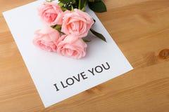 Rosa färgrosen med meddelandet av älskar jag dig Royaltyfri Bild