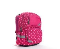 Rosa färgskolaryggsäck med vitprickar som isoleras på vit Arkivbilder