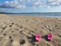 Rosa färgskor på stranden Royaltyfria Foton