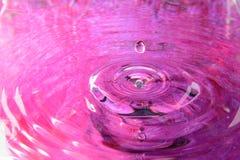 Rosa färgvattenreflexion och vattendroppe Arkivbild