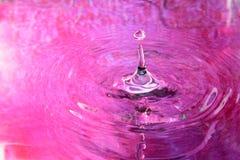 Rosa färgvattenreflexion och vattendroppe Arkivfoto