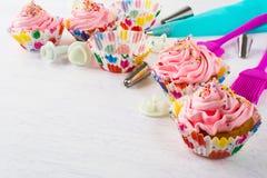 Rosa födelsedagmuffin och cookwarebakgrund Arkivbild