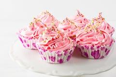 Rosa födelsedagmuffin på kakaställning Arkivfoto