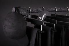 rosa försäljningsyellow Det svarta locket och flåsandet, jeans som hänger på kläder, rack bakgrund friday close upp Arkivfoto