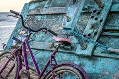 Rosa Fahrrad gelehnt auf Türkisfischerboot lizenzfreie stockbilder