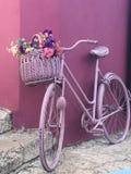 Rosa Fahrrad mit einem Korb voll von den Blumen stockfoto