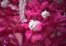 Rosa filialer av en konstgjord julgran med jultre royaltyfri fotografi