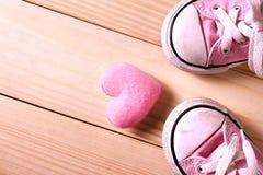 Rosa flickagymnastikskor med rosa hjärtor på ett trägolv Arkivfoton
