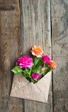 Rosa floresce no envelope do papel do ofício sobre o fundo de madeira Fotos de Stock
