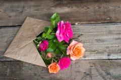 Rosa floresce no envelope do papel do ofício sobre o fundo de madeira Imagem de Stock Royalty Free